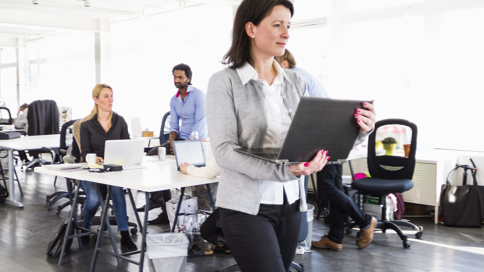 Woman with laptop walking among office tables.
