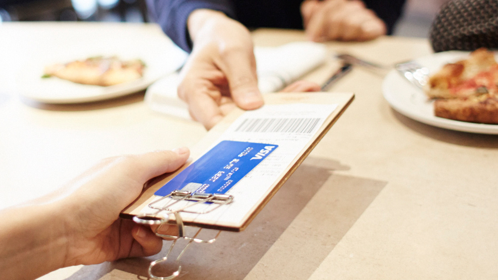 Person paying with Visa card over the counter.