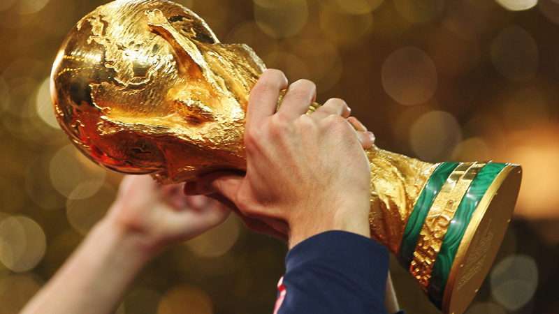 Hands holding FIFA trophy