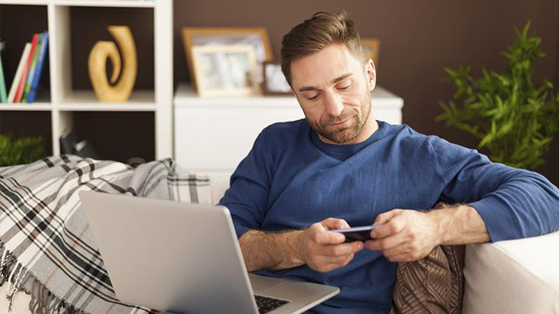 Man sitting on a couch with a laptop on his lap holding a smart phone with both hands.