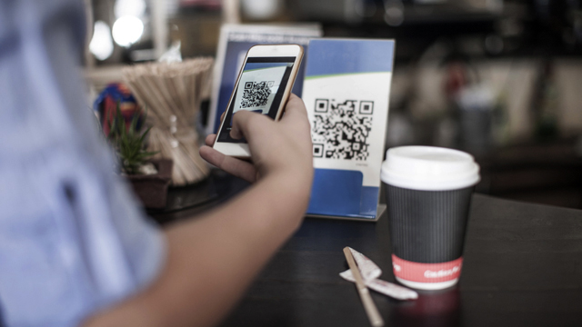 Person standing in front of a table scanning a qr code on his mobile phone.