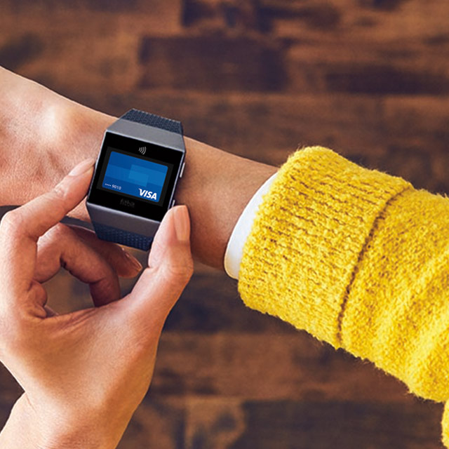 Woman using Visa Token on a Fitbit smartwatch.