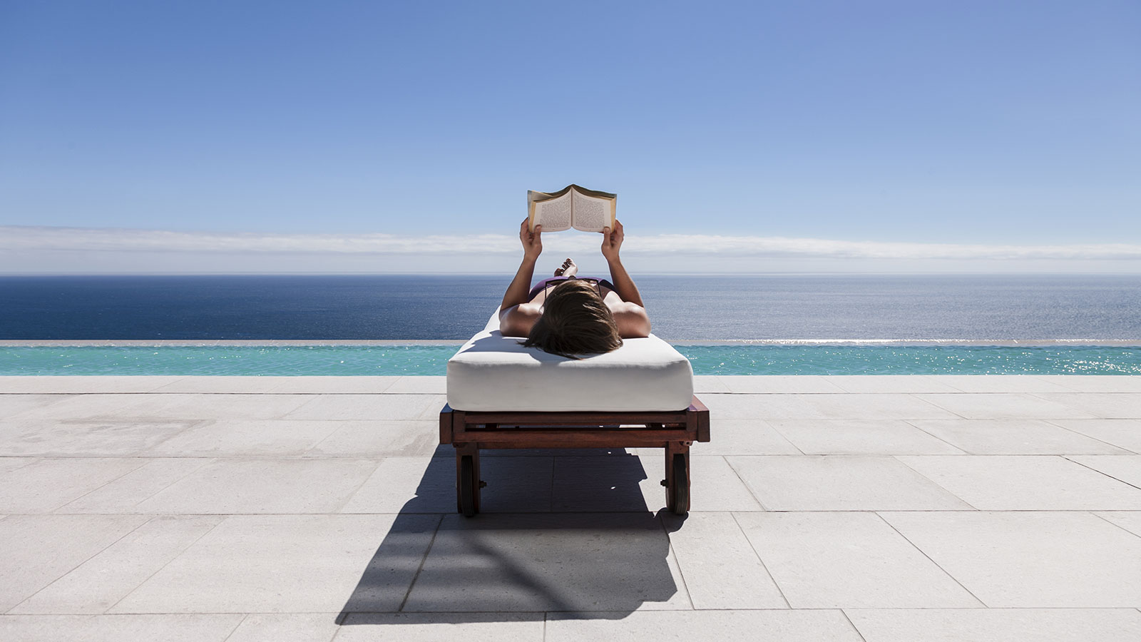 A woman reading a book while reclining on a lounge chair overlooking the beach.