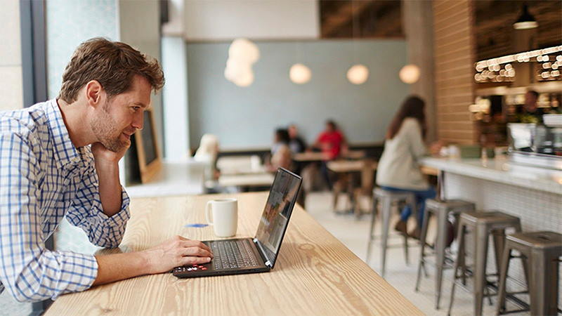 Man paying online via laptop in cafe